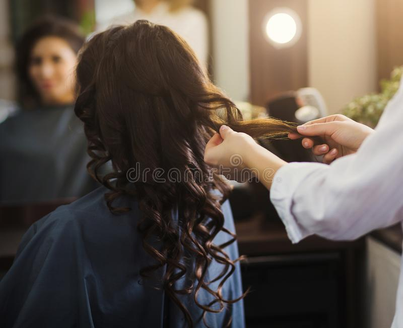 Hairdresser making curly hair to client stock photography