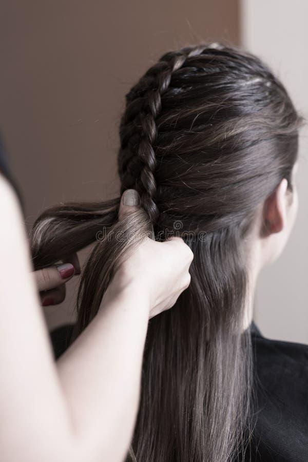 Hairdresser making a dutch braid. Close up of hands stock photo
