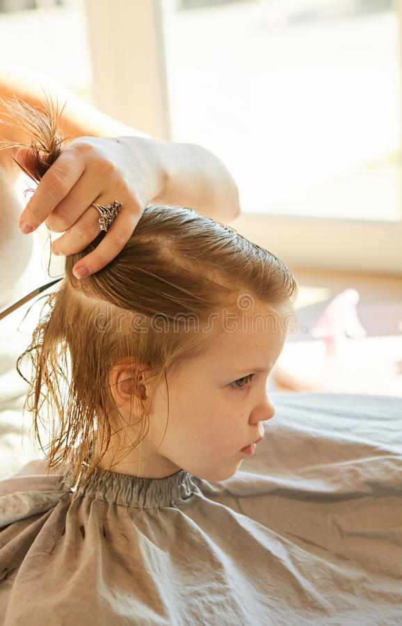Hairdresser making a hair style to cute little girl. royalty free stock photography