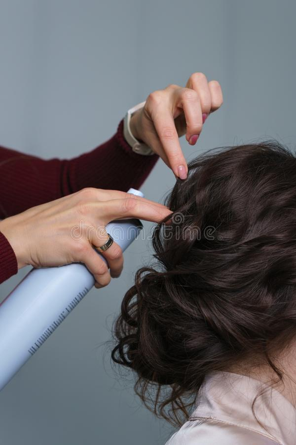 Hairdresser making hairstyle to girl in beauty salon stock photo