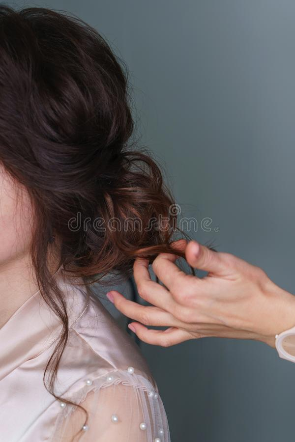 Hairdresser making hairstyle to girl in beauty salon. Hairdresser at work in process of creating wedding hairstyle. Hand hairdresser straightens brown curls stock images