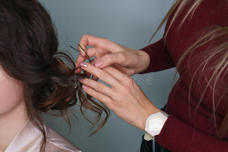 Hairdresser making hairstyle to girl in beauty salon. Hairdresser at work in process of creating a wedding hairstyle. Master fixes lower topknot of hair with royalty free stock photos