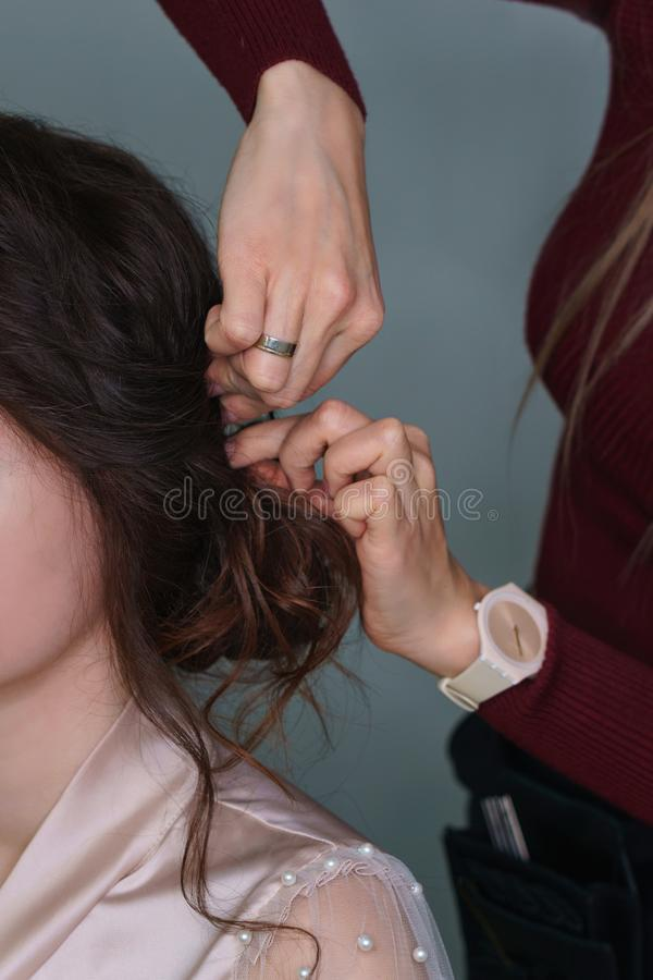 Hairdresser making hairstyle to girl in beauty salon. Hairdresser at work in process of creating wedding hairstyle. Master fixes lower topknot of hair with royalty free stock photo
