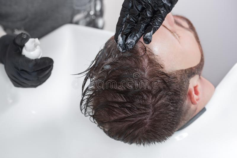 The hairdresser paints hair from gray hair of a man in a barbershop royalty free stock images