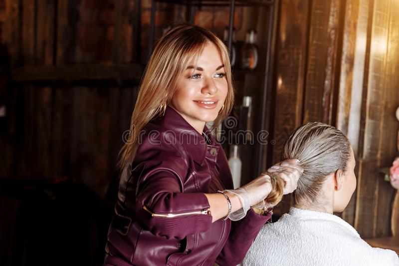 Hairdresser pulling hair of customer after applying the mask. Strong and healthy hair. Spa, hair clay, hair care stock photo