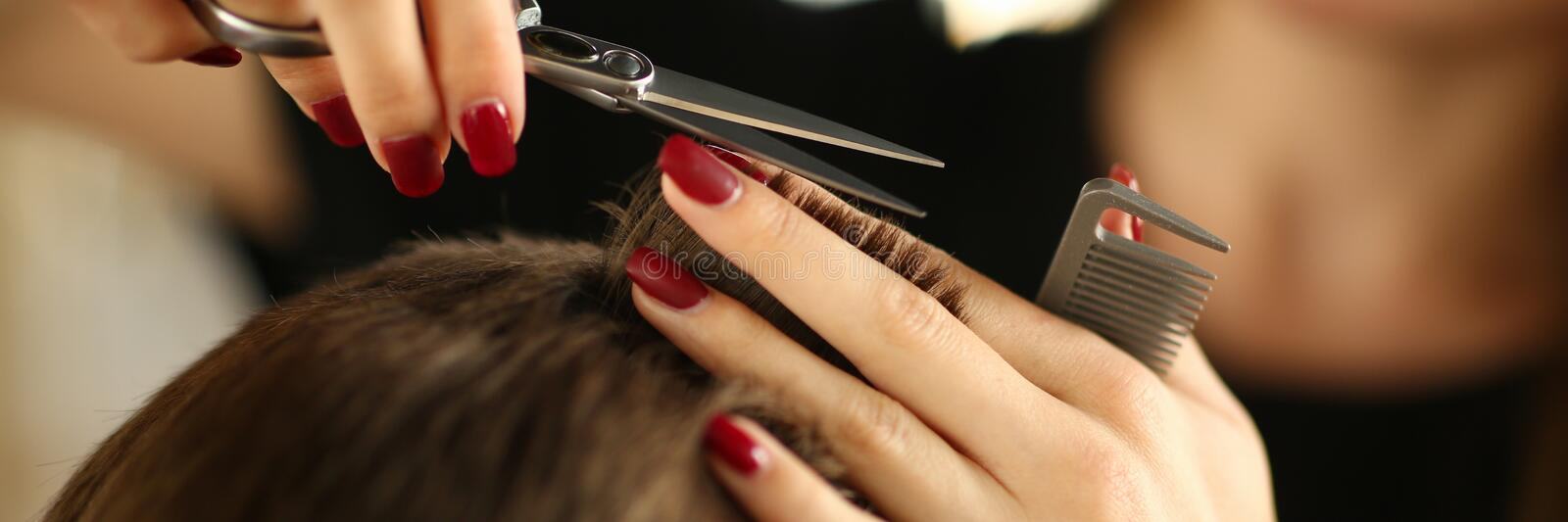 Hairdresser with Scissors Cutting Brown Male Hair. Hands with Red Manicure Making Haircut for Man. Female Fingers Holding Hairbrush for Client Hairstyle stock photos