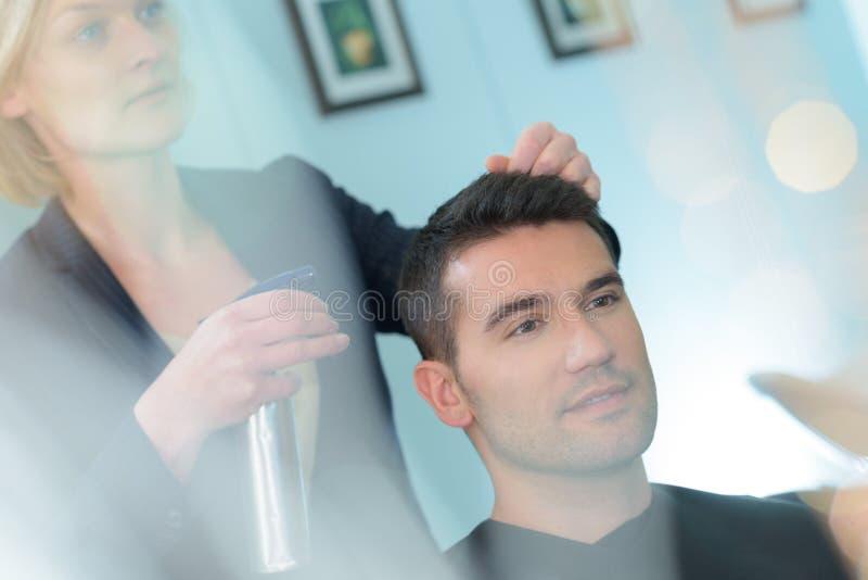 Hairdresser sprays handsome client stock photos