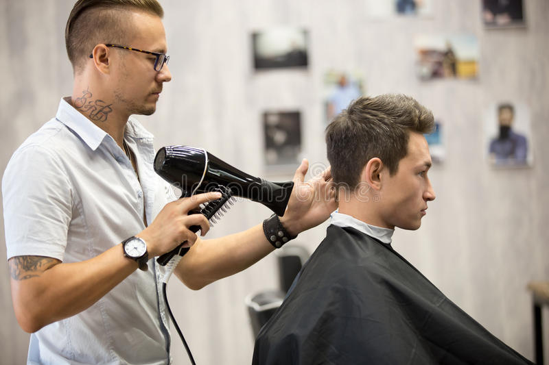 Hairdresser styling hair for male client royalty free stock photo