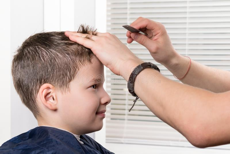 Hairdresser stylist makes a hairstyle for a boy with a comb royalty free stock photo