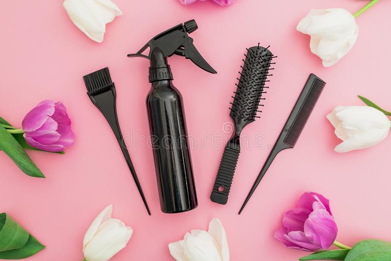 Hairdresser tools - spray, combs and tulips flowers on pink background. Beauty concept. Flat lay, top view stock images