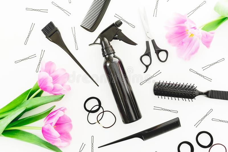Hairdresser tools - spray, scissors, combs, barrette and tulips flowers on white background. Beauty concept. Flat lay, top view stock photos