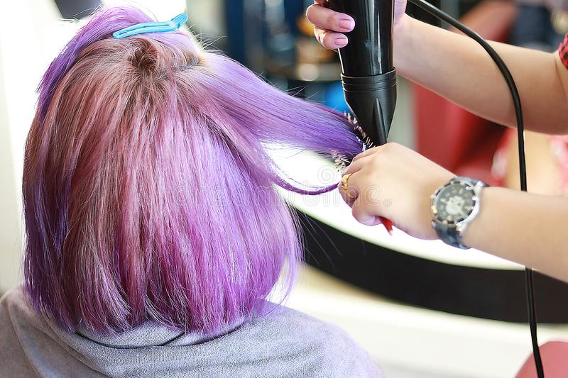 Hair drying on violet. A hairdresser use hair dryer and hairbrush on the violet short hair in salon royalty free stock photo