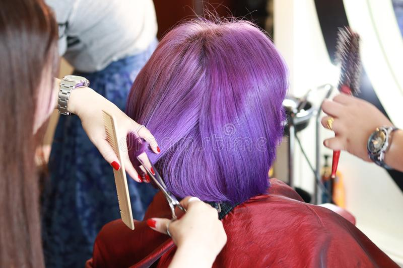 Cutting on the violet hair. The hairdresser used a hair trimming scissors cutting on the hair tips in salon royalty free stock photos