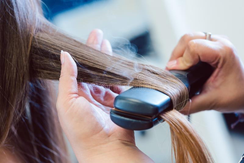 Hairdresser using flat iron on hair of woman customer stock photography
