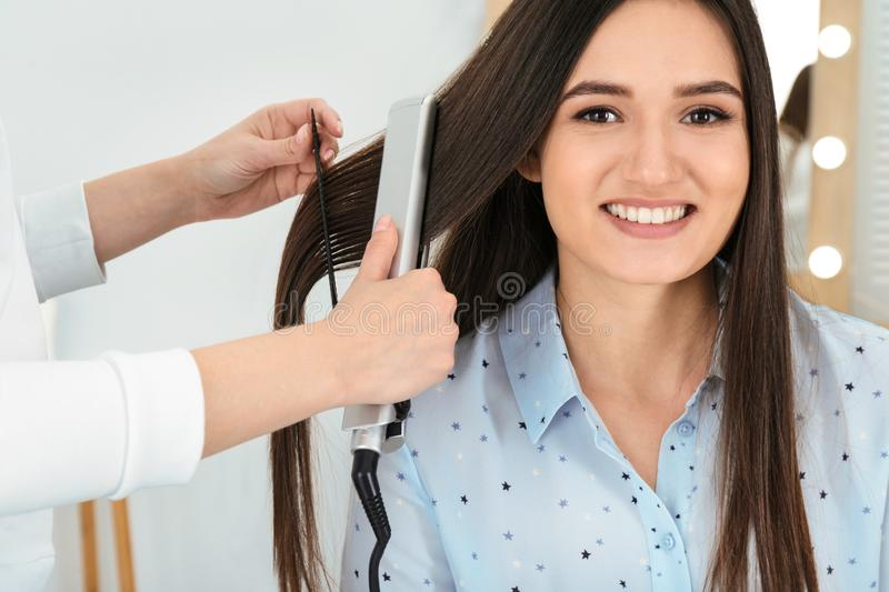 Hairdresser using modern flat iron to style client`s hair royalty free stock photo