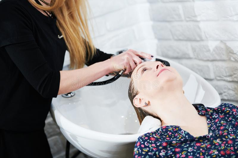 Hairdresser washing female blonde hair. Slow motion stock photo