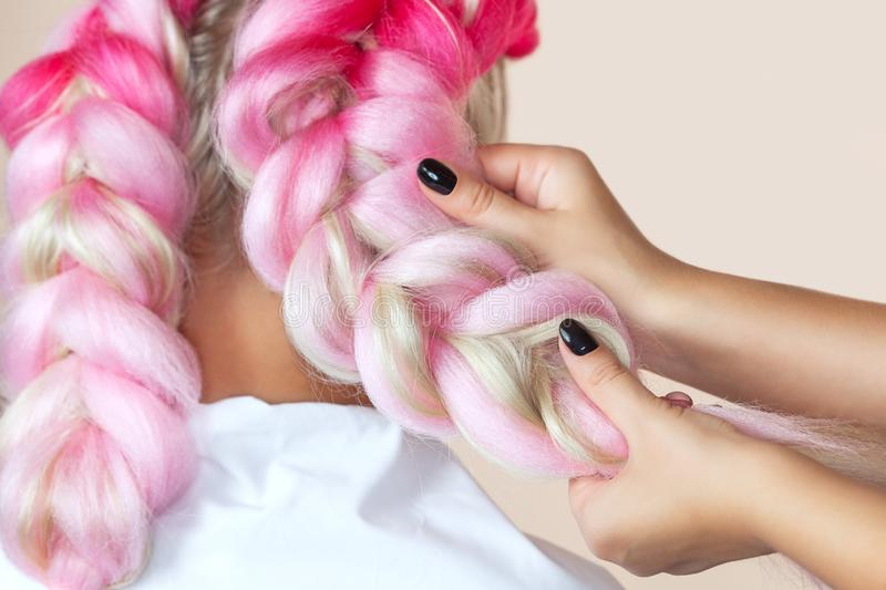 The hairdresser weaves braids with pink kanekalons beautiful blonde stock images