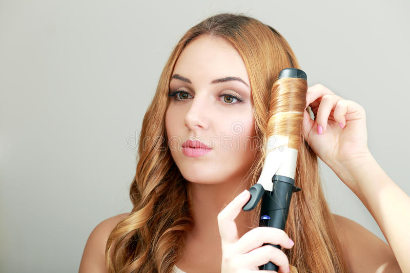 Hairdresser woman curls her hair royalty free stock images
