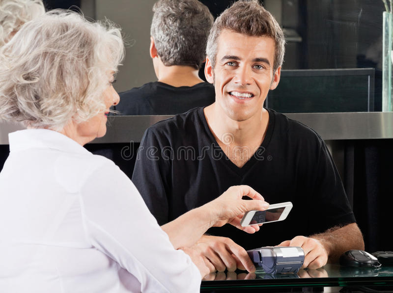 Hairdresser With Woman Paying Through Cellphone. Portrait of happy hairdresser with women paying through mobile phone at counter using NFC royalty free stock photos