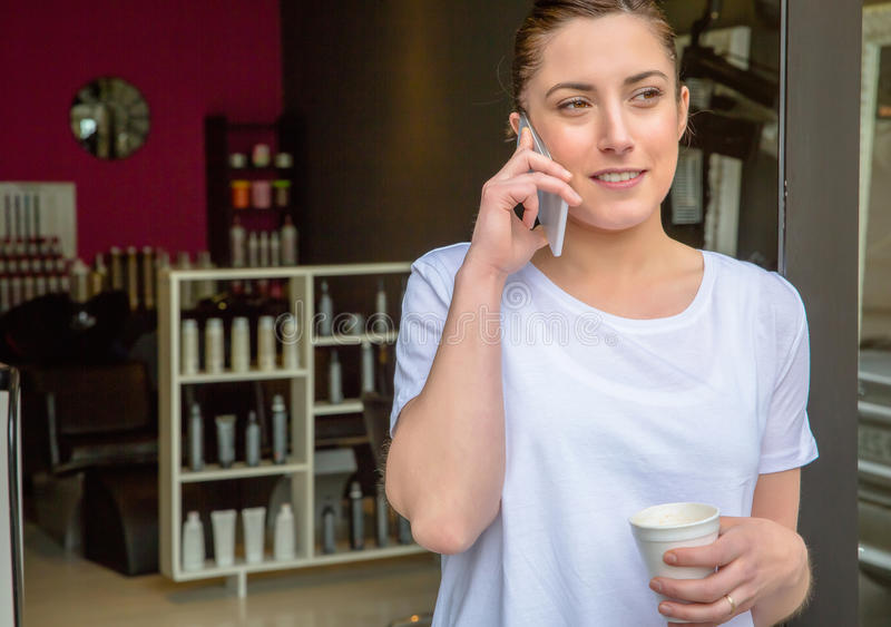 Hairdresser woman talking with smartphone in a royalty free stock photos