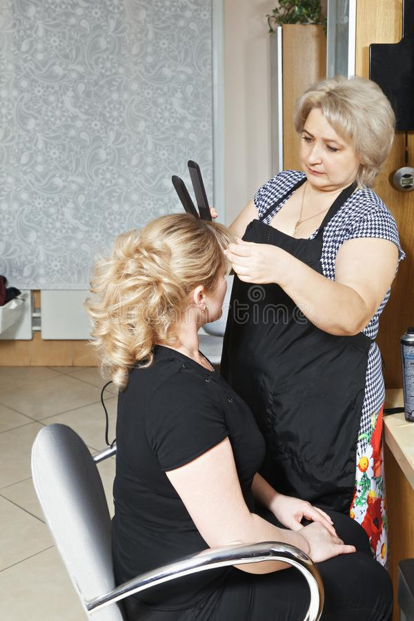 Hairdresser at work. Using curling tongs. Vertical shot royalty free stock images