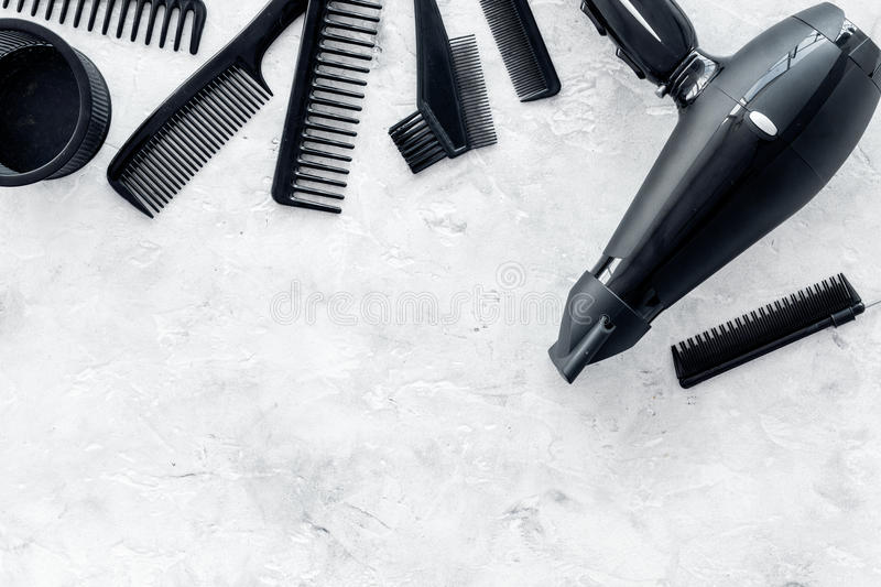 Hairdresser working desk with dryer and tools for hair styling on gray stone desk background top view mock up. Hairdresser working desk space with dryer and royalty free stock photography