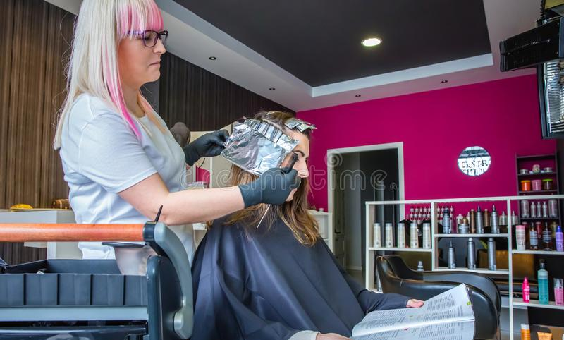 Hairdresser wrapping strands of woman hair with aluminium foil stock photography