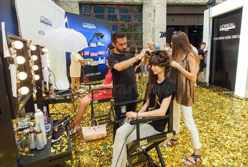 Hairdresser and young woman making new hairstyle in a pop-up beauty salon during popular outdoor party royalty free stock photos