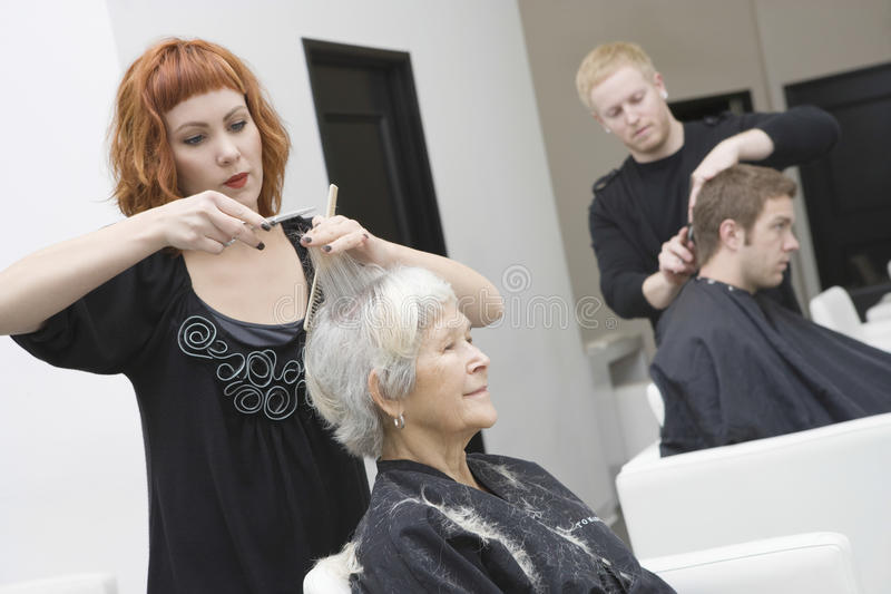 Hairdressers Giving Haircut To Customers stock images