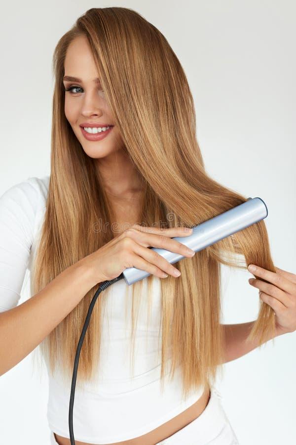 hairdressing Mulher com cabelo longo bonito usando o Straightener imagens de stock