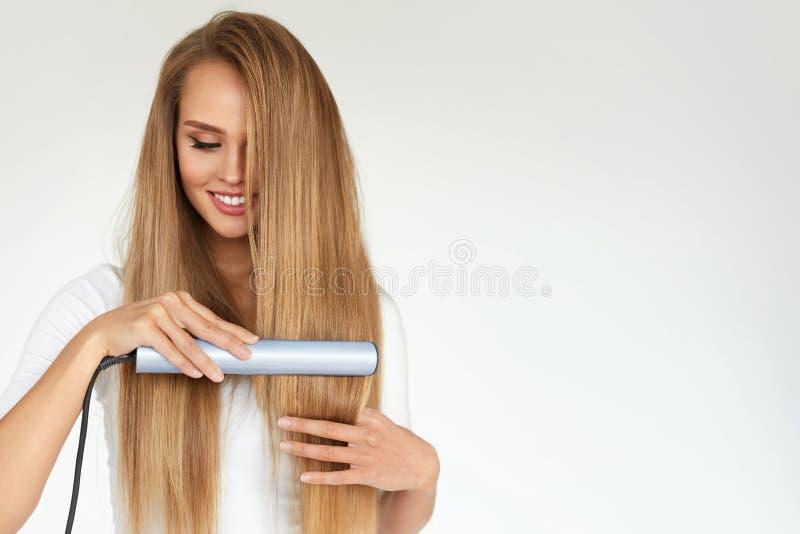 hairdressing Mulher com cabelo longo bonito usando o Straightener fotografia de stock