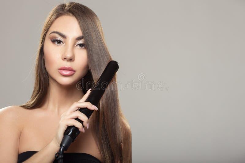 hairdressing Raddrizzamento dei capelli del ferro Bella donna con capelli diritti lunghi Capelli sani immagine stock libera da diritti
