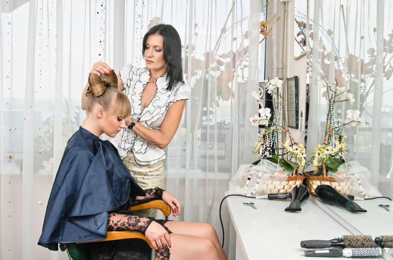 In hairdressing saloon. Woman making a coiffure in hairdressing saloon royalty free stock image