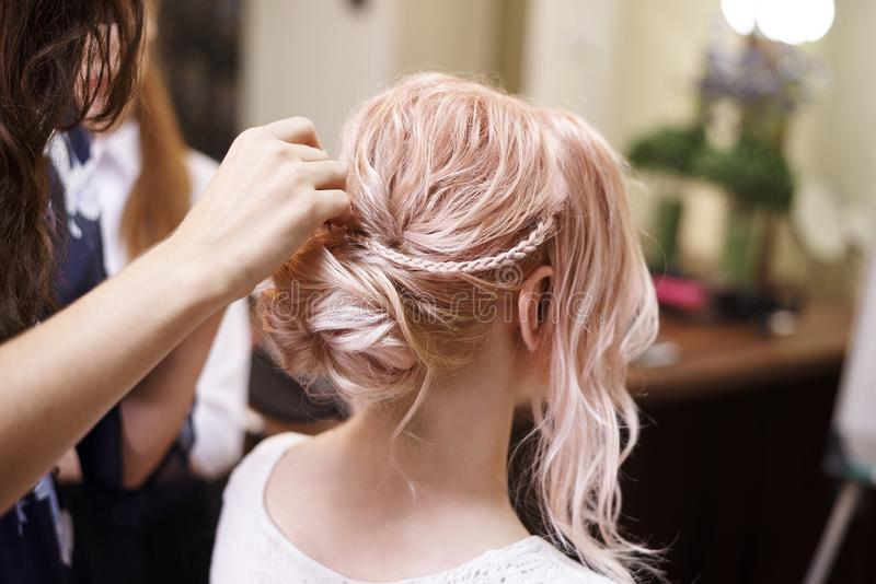 Hairdressing services.Сreating an evening hairstyle. Hair styli. Ng process stock photos