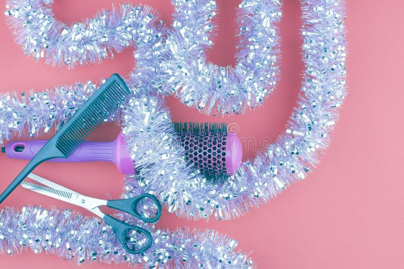 Hairdressing tools and Christmas tinsel on a pink background. stock images