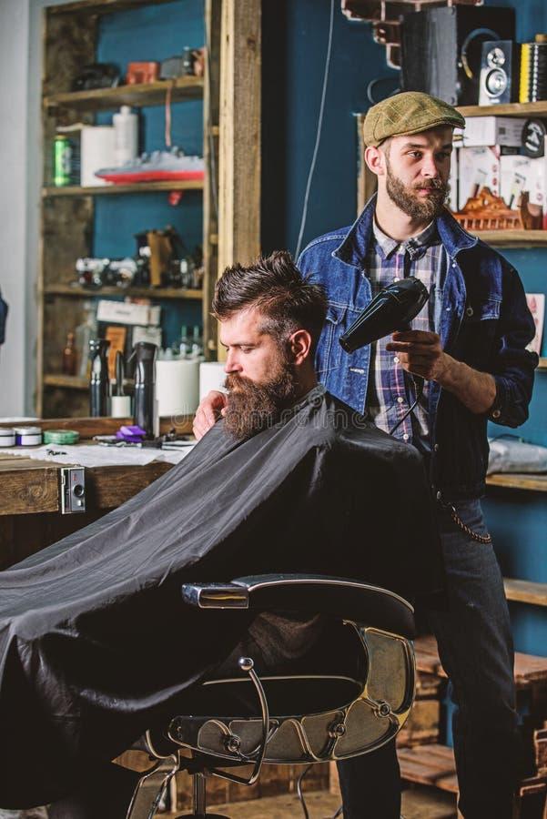 有hairdryer工作的理发师在有胡子的人理发店背景的发型 得到发型的行家有胡子的客户 免版税库存图片