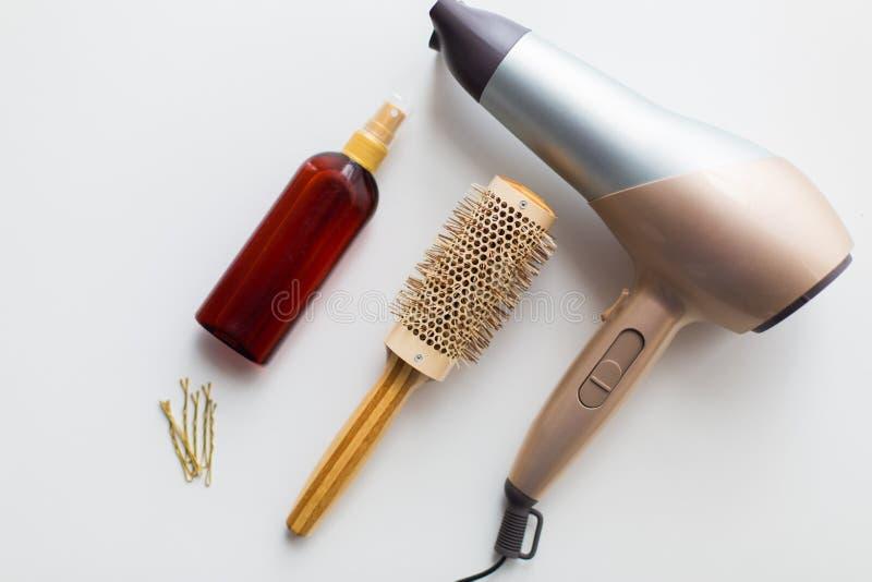 Hairdryer, cepillo, laca para el pelo labradora caliente y pernos foto de archivo libre de regalías