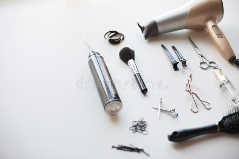 Hairdryer, scissors and other hair styling tools. Hair tools, beauty and hairdressing concept - hairdryer, scissors, comb and hot styling spay on white royalty free stock images