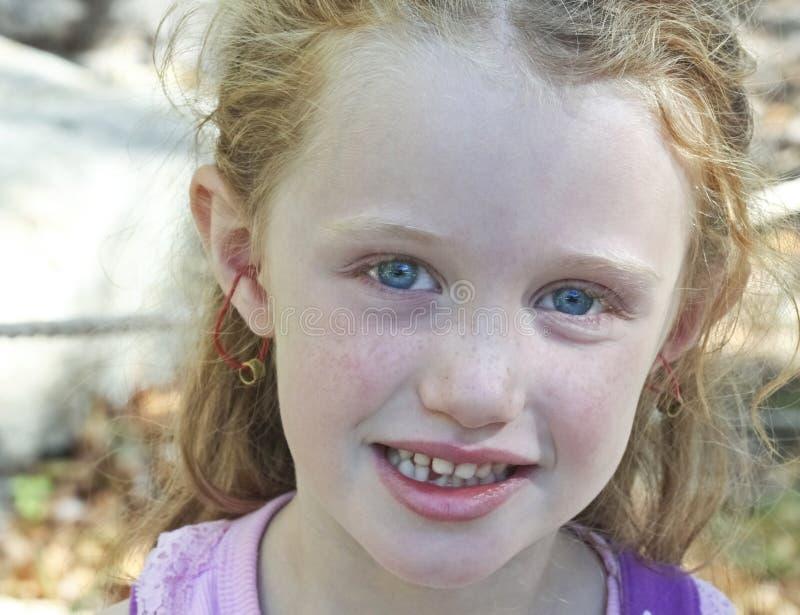 haired flicka för blåa ögon little som är röd arkivfoto