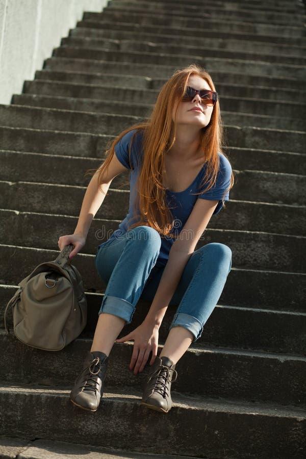 haired röd sittande trappa för flicka arkivbilder