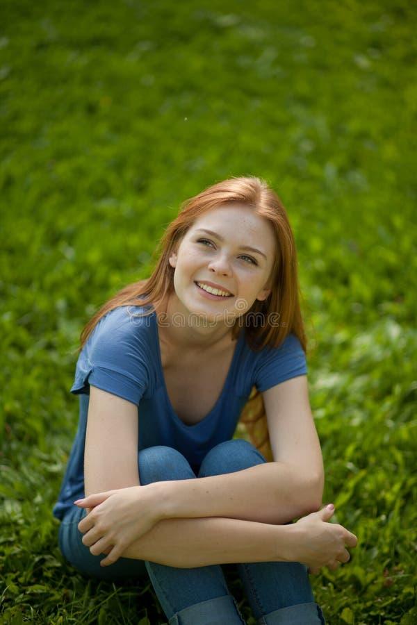 haired röd sitting för härligt flickagräs fotografering för bildbyråer