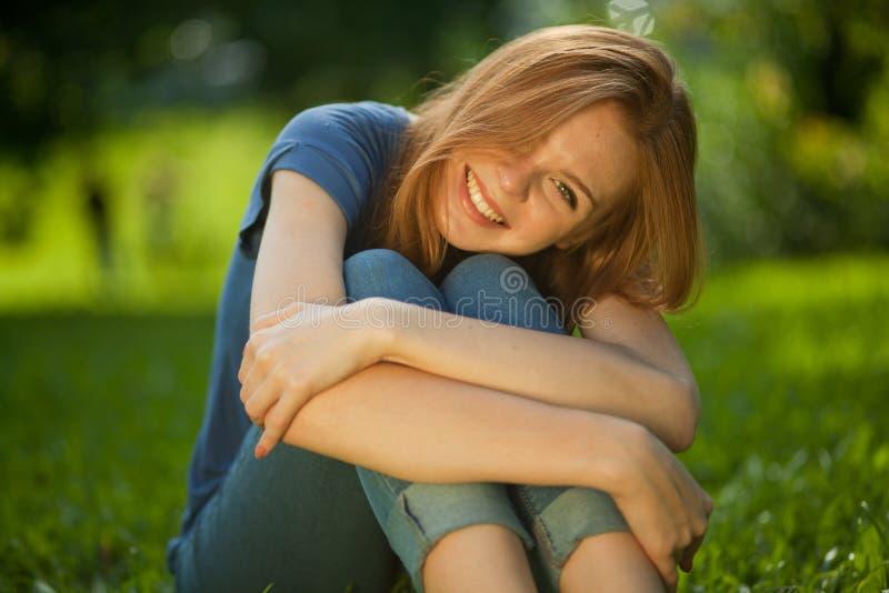 haired röd sitting för härligt flickagräs arkivbild