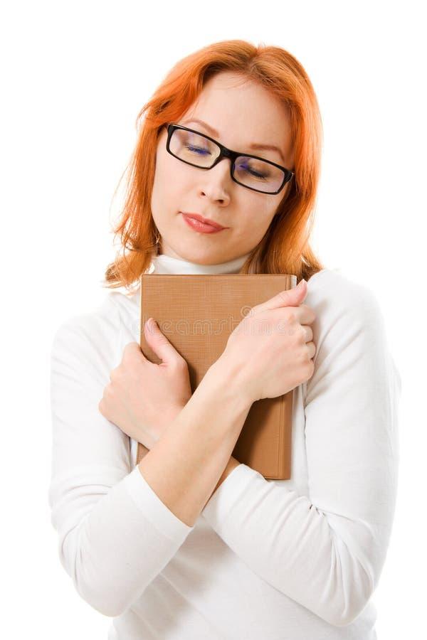 haired red för attraktiva bokflickaexponeringsglas arkivfoto