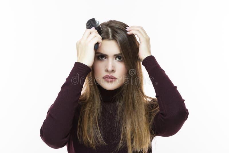 Hairloss en Kaalheidskwesties Jong Kaukasisch Wijfje die Haarproblemen hebben Het controleren van Haar in Haarborstel Tegen wit royalty-vrije stock afbeeldingen