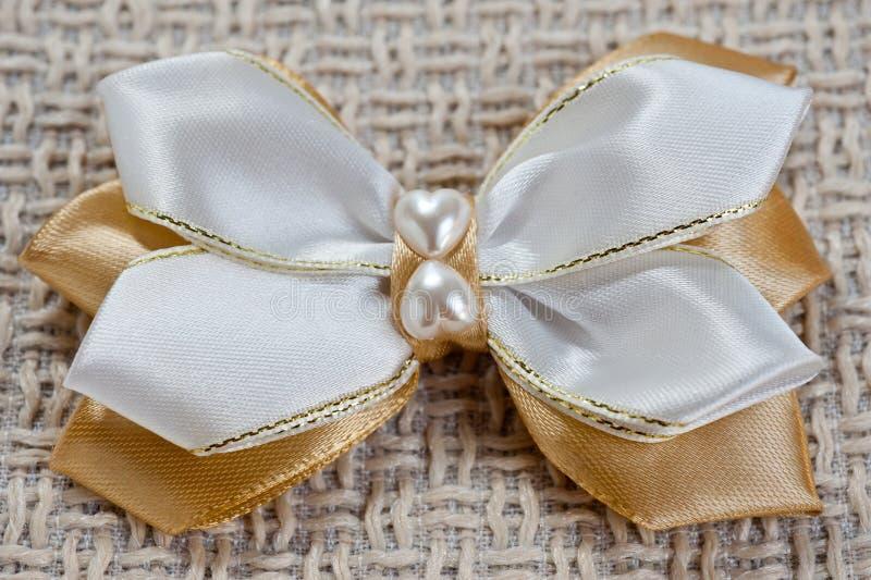 Hairpin dla łęku biel i złocisty kolor na tle prostacka tkanina, zbliżenie strzał obrazy royalty free