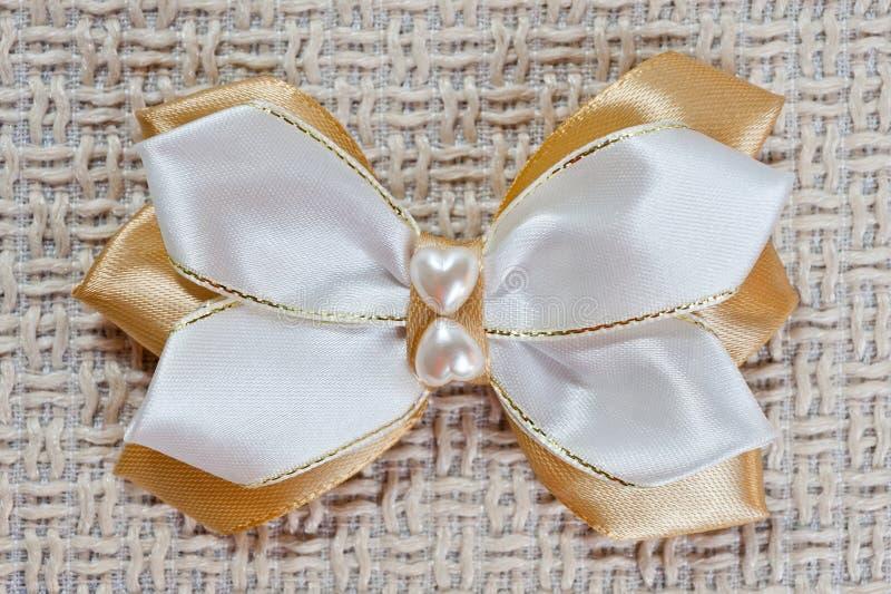 Hairpin dla łęku biel i złocisty kolor na tle prostacka tkanina, zbliżenie strzał fotografia stock