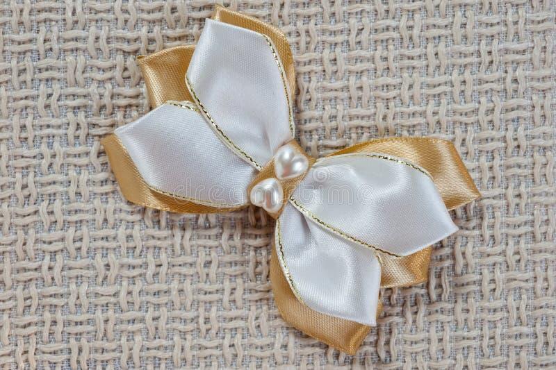 Hairpin dla łęku biel i złocisty kolor na tle prostacka tkanina, zbliżenie strzał zdjęcia stock
