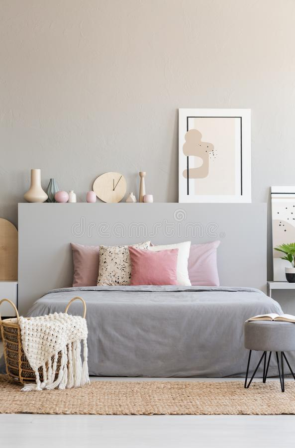 Hairpin pouf with book and knit blanket in wicker basket standing on carpet by the king-size bed in real photo of grey room inter royalty free stock photo
