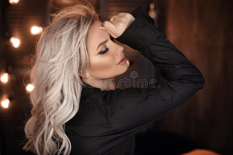 Hairstyle. Beautiful blonde woman portrait posing in black shirt. Fashionable blond girl model over bokeh lights dark background. Alluring female with beauty stock photo