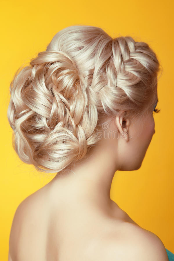 Hairstyle. Beauty Blond girl bride with curly hair styling over. Yellow background royalty free stock photos